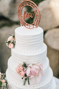Caitlin and Matt's Garden California Wedding by Kambria Fischer Photography | A simple white wedding cake fit right into the elegant garden theme with pink roses and a love woodcut cake topper.
