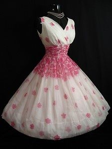 """1950's party dress in an exquisite floral print chiffon organza. There are two layers to the skirt – an ivory satin acetate lining, topped with a floating overlayer of white chiffon decorated in an exquisite pink floral print.  Label reads """"Junior Theme – New York""""."""