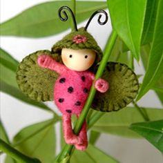 Watermelon Juicy Bug: Only body is felted, arms/legs covered in cotton floss, wood bead head and wire antenna. It's belly is made of nedle felted wool, the wings + hat are made of felt. This little bug is so cute & is poseable + will hold onto object.