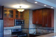 Condo kitchen renovation with recessed downlights in low-profile soffit against concrete slab ceiling.