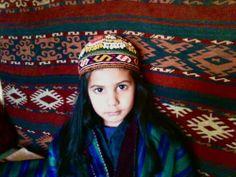 afghan girl... nice uzbek nomadic kilim, traditional hat