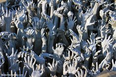 Hand reach up, symbolizing the way to happiness through overcoming cravings at The White Temple #Thailand