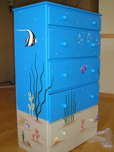 ocean theme nursery ideas   The tropical fish and coral turn his childs dresser into a ocean
