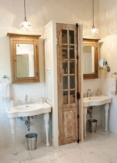 For the bathroom of a longtime customer-turned-friend, designer Katie Gagnon created a unique storage unit for the space between a pair of pedestal sinks. The storage cabinet was custom made while the door is a vintage salvaged piece. Vintage Bathroom Cabinet, Vintage Bathrooms, Bathroom Wall, Modern Bathroom, Master Bathroom, Bathroom Cabinets, Wall Cabinets, Bathroom Vanities, Chic Bathrooms