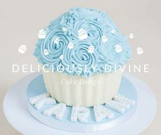Blue and white Giant cupcake for a boys cake smash photo shoot.  A vanilla cake with buttercream and jam filling, chocolate shell (bottom) and vanilla blue buttercream roses on top.  Used for a 1st birthday cake smash photo shoot.  Sweet, striking and cute this would be great for any boys birthday celebration, christening, or baby shower. To book or for more information email: lee-anne@deliciouslydivine.co.uk Made by deliciouslydivine.co.uk