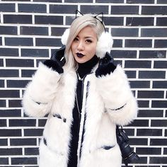 Love the contrast between her coat, gloves, earmuffs, lipstick, hair....and the black and white brick wall.
