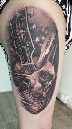 Skull with guitar black and gray tattoo on upper thigh, tattoo by Hong Kong Tattoo Artist : F Cheung