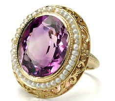 Seeded Vintage Beauty in an Amethyst Pearl Ring An oval natural faceted amethyst of approximately 6.5 carats reigns supreme with a surround of tiny natural seed pearls wired to the frame. The fancy filigree mount of 14k yellow gold is appointed with an openwork gallery decorated with scrolling designs and floral and leaf patterns. The hue of the amethyst is a captivating blend of lilac highlights with medium deep purples.