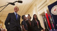 President Barack Obama laughs as Stephanie Bullock, 15, of Saint Croix, Virgin Islands, far right, explains her team's rocket design during the President's tour of the White House Science Fair. With Bullock are Maria Haywood, 12, and Shimeeka Stanley, 14