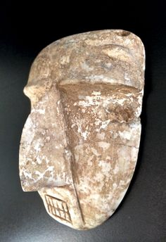 """Guerrero, the region from which this piece comes, is known for a wide variety of sculptural styles including Mezcala and Chontal. Ancient sculptors usually carved """"tecalli,"""" also called """"alabaster"""" or aragonite, a calcium carbonate stone found in caves. As with many Sultepec masks, the large aquiline nose dominates the face when viewed in profile, but the sublte modeleing of the cheeks and browline create a well-proportioned impression when viewed frontally."""