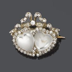A late 19th century moonstone and diamond brooch, circa 1890  The twinned heart-shaped moonstones surrounded by rose-cut diamonds, surmounted by a tied ribbon set with old brilliant and rose-cut diamonds, mounted in silver and gold, width 3.9cm.
