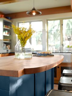 The curved detail on the island countertop shows off the thick edge-grain maple, while the dark blue base brings out its warm tones.   butcher block from @windfalllumber   Pendant shade over table from Jil Smith, insatiablestudios.com