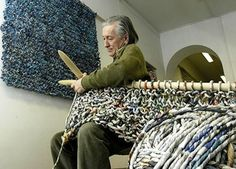 It's an optical illusion. In reality, the knitting needles and work are normal in size; the man is tiny.