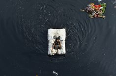 An Indian child looks on as he uses a makeshift raft to cross the Yamuna River in New Delhi, India, on February 28, 2015.