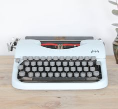 Machine à écrire vintage de couleur bleue ciel pour déco. Elle fonctionne mais les lettres ne reviennent pas toujours en place (à réviser pour s'en servir). Elle est complète avec son ruban bicolore rouge et noir.  On aime : son look année 60 et sa couleur pastel  Objet très lourd  Possibilité de retrait à l'atelier de Bordeaux sur rendez-vous