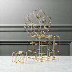 Shop 3-piece brass wire cube set.   Handcrafted in brass-plated iron, welded cubes construct a modular geometric sculpture.  Small, medium and large wire grids freestand, stack, wall-mount or suspend.