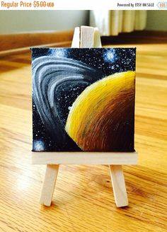 ❘❘❙❙❚❚ ON SALE ❚❚❙❙❘❘     This tiny painting of Saturn measures only 2.5 x 2.5! The painting was completed using high-quality acrylic paints on a real, miniature stretched canvas that measures approximately 1/2 deep. The painting has been sealed in a water resistant sealer and will be lovingly packaged in glassine. This painting comes with a miniature easel that holds miniature paintings up to approximately 4x4 and could also be used for ATCs, ACEOs, photographs, and other small works of…