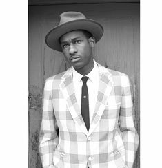 Leon Bridges is wearing a plaid jacket, skinny tie and classic white button up.