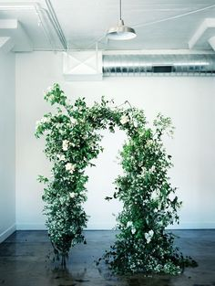 Bring Spring indoors with a wild and lush arch. Utilizing the fresh greens in this industrial space is very unique