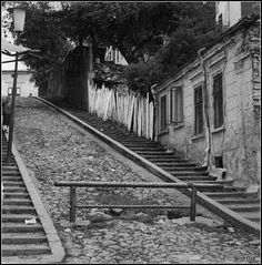 """Povestea străzii Pelerinilor(""""Scăricica"""", cum o numește Henri Stahl), dispărută în urma sistematizării Uranus-Rahova.  """"E un pitoresc drum, bolovănos, ce urcă, treaptă cu treaptă, greoi, din Strada Puţu-cu-apă-rece, până sus în dosul cazărmilor din strada 13 Septembrie, unde-ţi apare, peste pomii şi casele din coastă, nesfârşita veselă grădină a mahalalelor bucureştene, iar pe vreme limpede, în zare, silueta albastră a Carpaţilor, cu tăietura caracteristică a Bucegilor.  Trec puţini prin ..."""