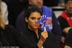 Giving a hand: The 19-year-old model tried to be apart of the cheer squad with a blue and white hand clapper