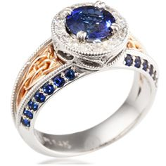 This ornate engagement ring has vintage design elements.  It has a millegrained halo of 1.5mm accent diamonds or sapphires.  The head has a pierced, millegrained gallery.  The center stone is set low with double prongs.  A Celtic trinity knot fills the recesses of the split shank and tapers towards the palm.  Bead-set gemstones follow channels along the band. The narrowest part of the band is 4mm wide. Priced with 0.6 carat total weight stones, and in your preferred metal/s.  Can you imagine…