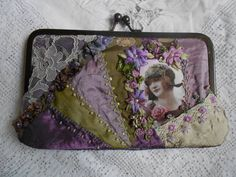 I ❤ crazy quilting & embroidery . . . (translated) Clutch made of fabric. Technique crazyquilt. Embroidered with silk ribbon hand dyed & imported beads. Made of taffeta, lace & other fabrics used for parties. Lined in lilac taffeta. Embroidered on front only, with the back in purple taffeta. Close in old gold metal. ~By Iris Lins