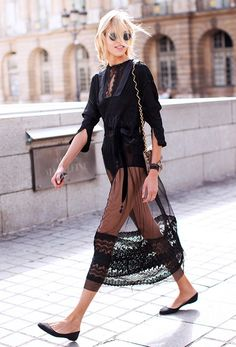 Anja Rubik layers a sheer black lace dress over a button-down shirt and black bodysuit