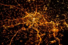 The brightly lit core of the Liège urban area appears to lie at the center of a network of roadways—traceable by continuous orange lighting extending out into the rural and relatively dark Belgian countryside.