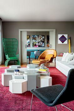 Quer o cinza nas paredes, porém deseja um ambiente repleto de vida? Tapete e móveis de cores inusitadas, como vermelho, verde e azul, criam o contraste necessário com peças brancas. Clique na imagem para ver mais!