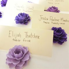 Set of 50 mini cardstock paper blossom place card holders in 5 shades of purple. 10 of each color.  These mini paper blossoms can be used in other ways as well. A few favorites include: -decoration in place of confetti or table scatter to surround centerpieces (each order is good for 1-2 tables/centerpieces) -embellishments for handmade cards or scrapbook pages -wedding favors toppers -escort or place card embellishments -place card holders  Each flower measures 1 inch in diameter and depth…