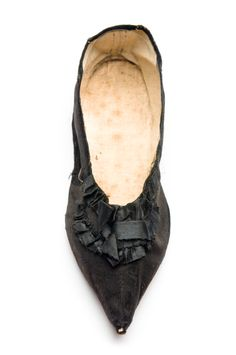Silk slipper, early 19th century. This straight (no specific left or right) has a slat sole, pointed toe and ruched silk ornamentation. Charleston Museum