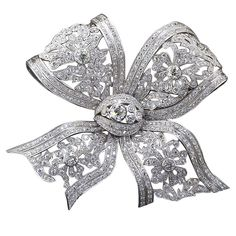 Large Diamond Bow Brooch, Magnificent large ornate diamond and platinum tied bow brooch. Largest diamond is approximately 3.50 carat old European cut with four more diamonds ranging 1.50 carat to 2.50 carat. Hundreds of smaller diamonds are inlaid along the edges and the flowery design. Intricate ribbon design exudes charm, elegance and fine craftsmanship. 20th Century.