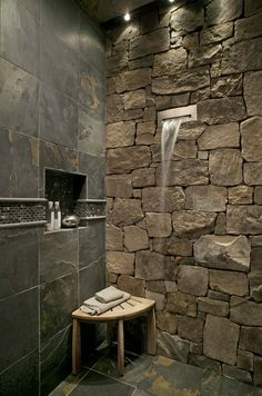 Natural Stone Wall inside Bathroom Shower Ideas with Waterfall Like Shower Faucet and Corner Table