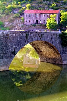Bridge and reflections    Old traditional house and stone bridge reflected in the river. Rijeka Crnojevica, Montenegro