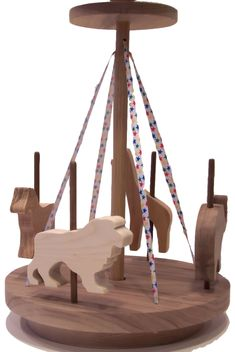 "For little girls and boys, our merry go round includes a horse, elephant, giraffe and lion. The colorful ribbon and ingenious design cause it to """"go round"""" with a toddler's help. Crafted out of oak,"