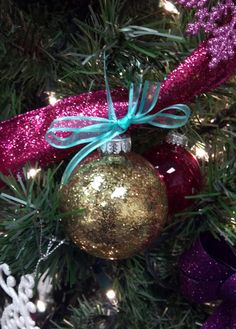 Homemade gold glitter ornament with teal ribbon