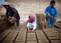 OBJETIVO 8: TRABALHO DIGNO & CRESCIMENTO ECONÔMICO Crianças afegãs empilham tijolos na fábrica de tijolos Sadat Ltd., onde trabalham diariamente das 8h às 17h em Cabul, Afeganistão8 - Majid Saeedi/Getty Images