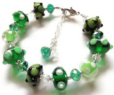 "Beautiful Shades of green Lampwork Bead & Crystal Bracelet.  Green LampWork beads I have added Austrian crystals and sterling silver beads. I have strung all of the beads on heavy, high quality stainless steel wire and added a good lobster claw closure.  The bracelet is a wearable 7.5"" long, plus I have an extender so that it will fit most any size wrist. $12.99"