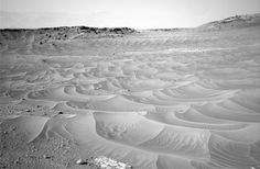 At first glance you'd be forgiven for thinking NASA's Mars rover Curiosity had stumbled across a wind-rippled lake or sea at the base of Mount Sharp.