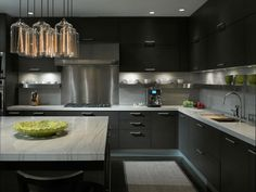 Kitchen - Gorgeous cabinetry with under cabinet lighting plus the stainless steel shelf for easy access to every day essentials surrounds the work area.  A multitude of clustered lights add impact over the island.  Very chic.  (repinned photo only from Gary Lee Partners)