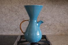 """A unique coffee carafe, with a wicker handle and a """"Chemex"""" drip style design"""