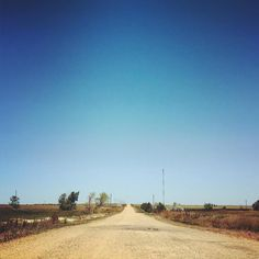 the road is empty silent stretches on forever --endless infinite-- takes you where you are going or perhaps nowhere at all the road is nothing the road is everything if you listen to its call  #road #dirtroad #sky #blue #west#travel #southdakota #poem #poetry #art #artist