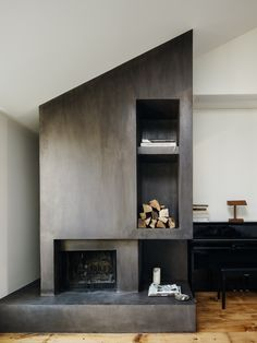 Dramatic, trowel-finished concrete fireplace complete with built-in firewood storage. Walls in Benjamin Moore White Dove.