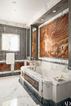 In a California villa designed by Juan Pablo Molyneux, a bath is paneled in distressed oak, gray onyx, and red marble; the tub surround is made of Calacatta marble from Carmel Stone Imports, and the tub fittings are by Waterworks.