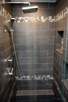Large tiles with smaller accent strips. Shower with Emser Tile's Lucente Concordia and Strands Twilight.