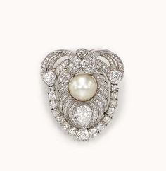 AN ART DECO DIAMOND AND PEARL PIN, BY KOCH  Designed as a single-cut diamond openwork plaque, centering upon a white button pearl within a pear and single-cut diamond scroll, to the old mine and European-cut diamond trim, mounted in white gold, circa 1920