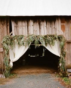 Eucalyptus branches are woven together and draped around the frame of this ceremony entrance