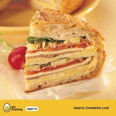 Hearty Omelette Loaf | Eggs.ca | #GetCracking #Eggs #Sandwiches Make this hearty omelette loaf for your next party or special brunch. Fill a crusty round loaf with layers of omelette, roast beef, Gruyere cheese, tomato, artichokes, lettuce, deli chicken slices and a creamy Caesar dressing for kick.