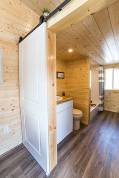 This tiny house bathroom has a 10' closet/storage area, a full bath tub, and side-by-side washer and dryer!